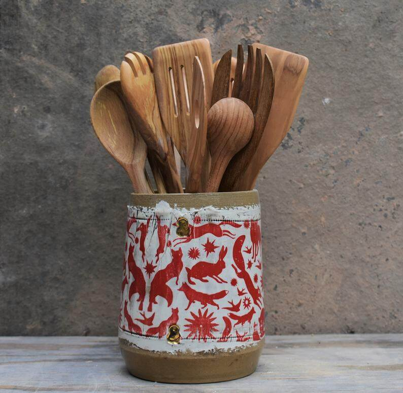Rustic utensil holder with red animals