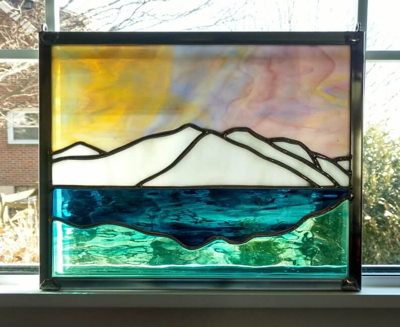 Stained glass window panel with mountains